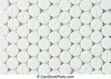 White tablets or medicine in rows forming background