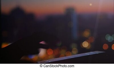 Woman using her Mobile Phone on beautiful blurred city background with bokeh. 1920x1080