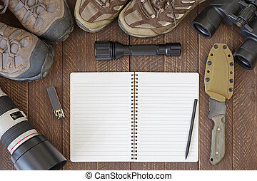 Top view of blank notebook with dirty hiking shoes,...