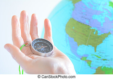 Hand holding a compass with North America on a globe in the...