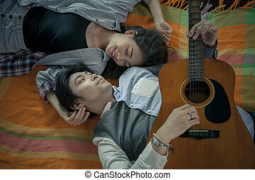 couples of asian younger man and woman playing guitar with...