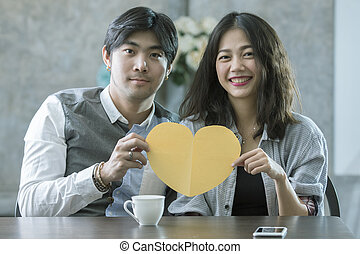 couples of asian man and woman holding heart shape paper cut