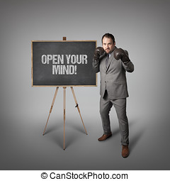 Open your mind text on blackboard with businessman - Open...