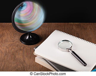 spinning globe and notebooks with a magnifying glass