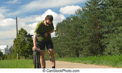 Cyclist man checks a bicycle wheel. The young man in the cycling shorts and sunglasses. Slow motion