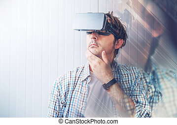 Man with VR goggles exploring virtual reality content and...