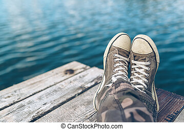 Man with crossed legs relaxing on riverbank pier