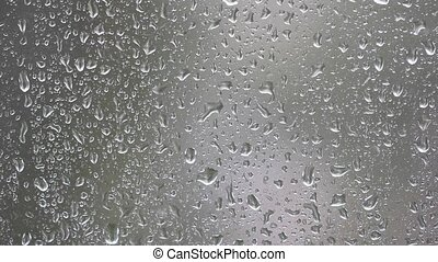 Close-up of water drops - Raindrops running down a window....
