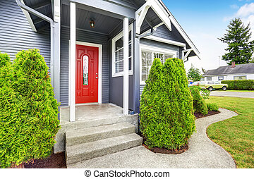 Classic American house with siding trim and red entry door -...