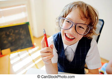 Funny little schoolboy in glasses sits at a school desk. It...