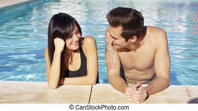 Handsome brown haired couple in blue pool on sunny afternoon...
