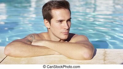 Man stands alone in pool and smiles at camera on a bright...