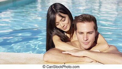 Handsome smiling couple cuddles in swimming pool on lovely...