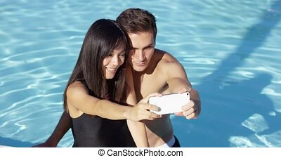 Beautiful woman in black swim suit takes photo with...