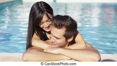Beautiful woman cuddles with her boyfriend in pool on a...