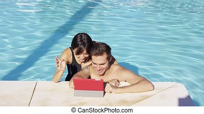 Smiling couple in swimming pool use digital device on a...