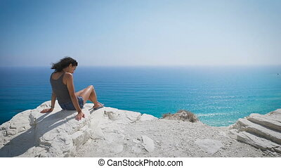 A young woman sitting by the sea