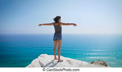 A young woman standing by the sea. Enjoying the fresh air -...