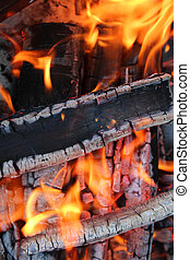 Flames on wood background - Charred wood and bright flames...