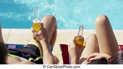 Couple relaxing at the pool with beers enjoying their summer...