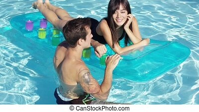 Happy young couple floating on mattress in pool - Happy...