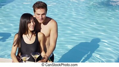 Loving couple smooching at swimming pool while keeping...