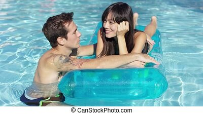 Young couple in love relaxing in the pool