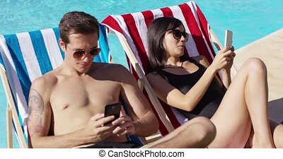 Young couple using phones at the swimming pool