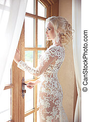 Beauty Portrait of elegant bride in wedding dress looking at window