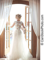 Young bride in gorgeous wedding dress with voluminous skirt...