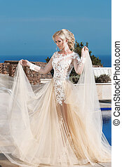 Happy blond bride in fashion wedding dress with blowing...