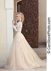 Elegant bride in fashion wedding dress posing by the wall....