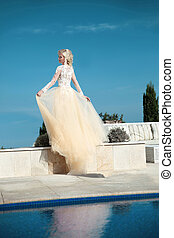 Beautiful bride in gorgeous wedding dress with blowing skirt...
