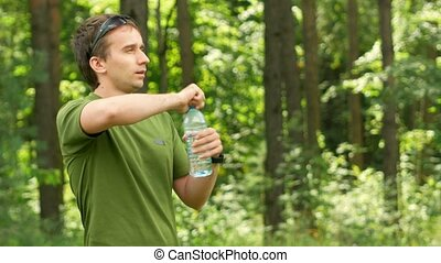 Young male cyclist drinks water from a bottle in the park. Green T-shirt and sunglasses