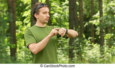 Young man touches the smart watch in a park Green T-shirt...
