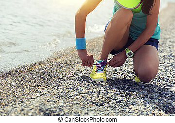 woman runner tying shoelace before running on beach