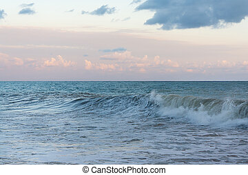 Sea waves against cloudy sky in the evening before the storm