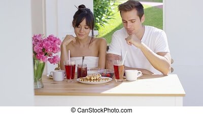 Couple having breakfast at outdoor table with pink flowers...