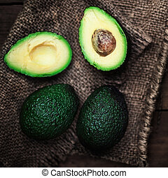Halved avocado and whole  over rustic background