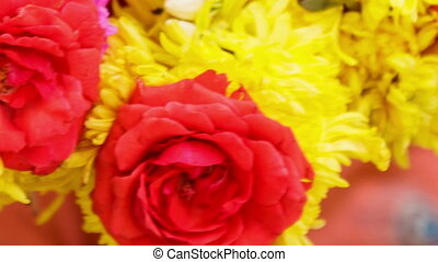 Woman Hands Compose Yellow Red Flower Garland - closeup...