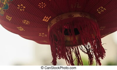 Wind Shakes Chinese Lantern Bottom by House Wall - closeup...