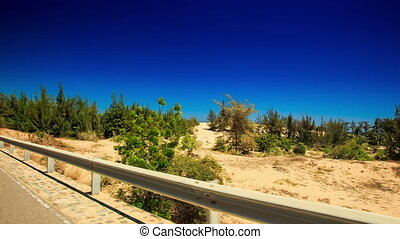 Camera Moves by Road Side Barrier and Sand Dunes - camera...