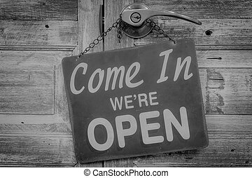 Come In We're Open on the wooden door. Black and white...