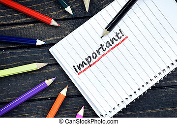 Important text on notepad and colorful pencils