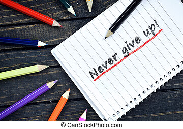 Never give up text on notepad and colorful pencils