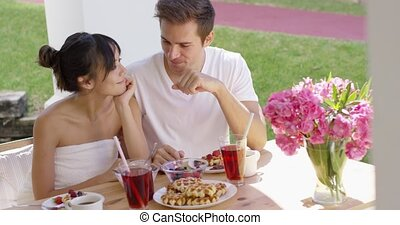Couple talking at breakfast table outside - Young couple...