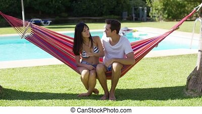 Loving couple in hammock kissing each other with swimming...