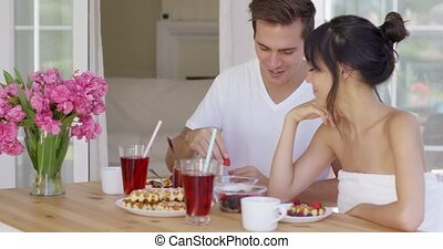 Man feeding his wife fruit at breakfast - Smiling man...