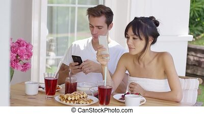 Woman showing man something on her phone - Beautiful young...