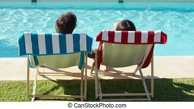 Couple relaxing in colorful deck chairs poolside - Couple...